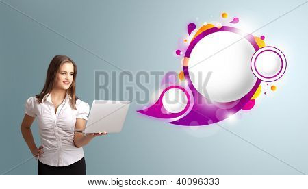 attractive young woman holding a laptop and presenting abstract speech bubble copy space