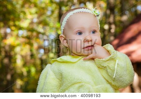 little beautiful baby girl in autumn park