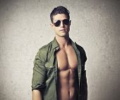 Shirtless young man with the shirt opened and sunglasses