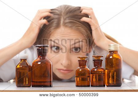 woman doctor or nurse with medication in glass bottles