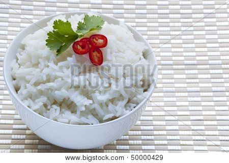 Bowl of white rice garished with sliced red chili and cilantro.