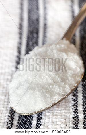 Sea salt flakes on old spoon.