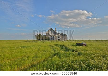 a deserted farm house is surrounded by prairie grass