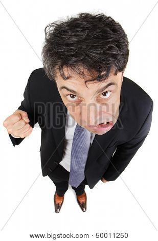 Humorous high angle full length portrait of an angry businessman glowering from under his eyebrows at the camera while growling and making a fist, isolated on white