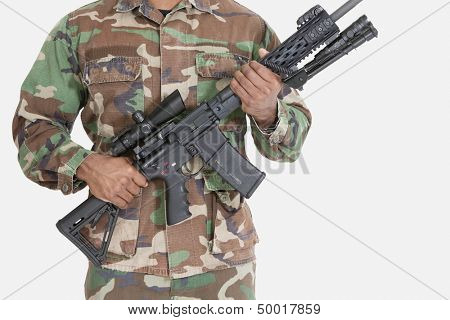 Midsection of US Marine Corps soldier holding M4 assault rifle over gray background