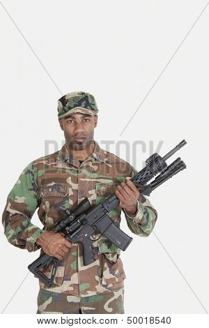 Portrait of young African American US Marine Corps soldier with M4 assault rifle over gray background