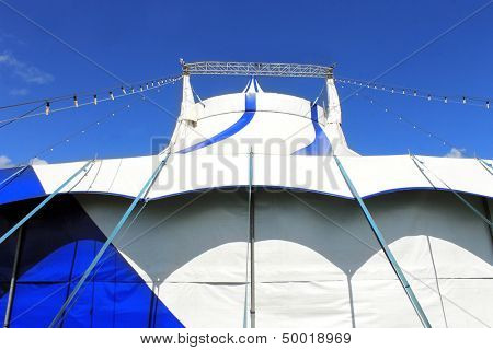 Low angle view of circus big top tent, blue sky background.