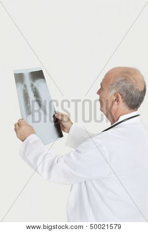 Senior male doctor examining medical radiograph over gray background