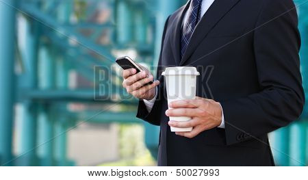 Close Up Of The Hands Of The Businessman With A Mobile Phone And Cup Of A Coffee