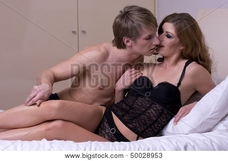 intimate young adult couple during foreplay in bed