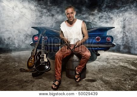 Guitarist at a garage next to the retro car in smoke