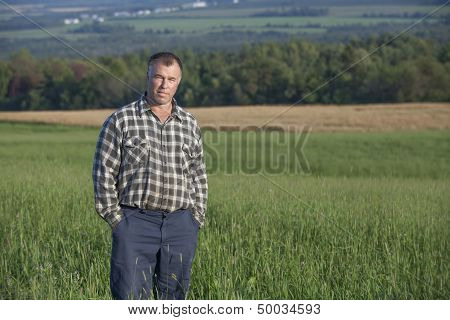 Proud farmer standing in one of his cultivated fields