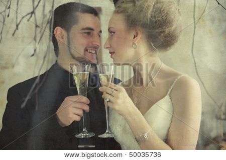 bride and groom holding  glasses with champaign in vintage room