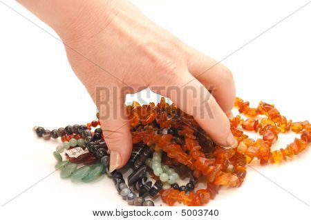 The Female Hand Holds A Beads On A White Background