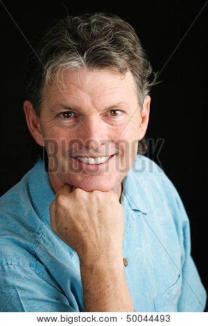 Portrait of handsome, smiling middle-aged man on black background.