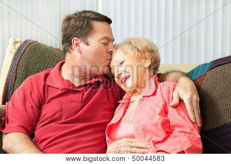 Senior woman gets a kiss from her loving adult son who has come to visit her in the nursing home.