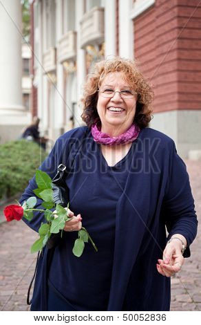 happy smiling senior lady, holding rose outdoors