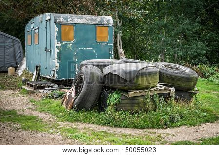 A Pile Of Old Tyres In Front Of An Abandoned Caravan