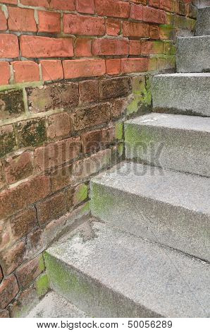 Stairs against an old brick wall