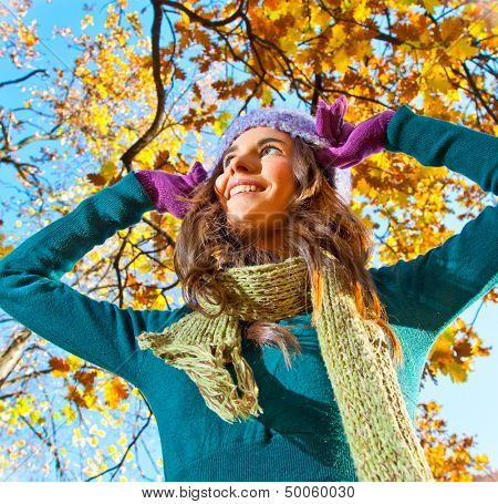 Beautiful girl with leaves on an sunny autumn-day in park