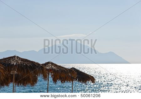 Sunshades made from palm branches and a Holy mountain Athos in background