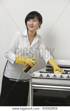 Young maidservant looking away while cleaning stove against gray background