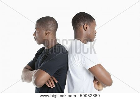 Two male friends standing back to back over gray background