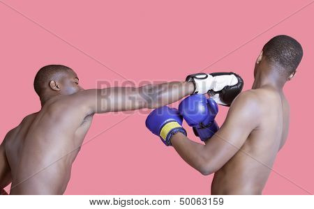 African American boxer punching opponent over pink background