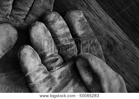 Artistic black and white image of well worn leather work gloves on wood background.  Low key still life with directional, natural lighting for effect.