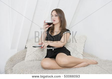 Young woman having a drink on sofa while changing channels with remote control