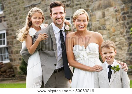 Bride And Groom With Bridesmaid And Page Boy At Wedding