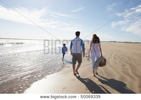 Rear View Of Family Walking Along Beach With Picnic Basket