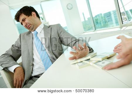 Image of disgusted male employee moving dollar bills away and refusing to take bribe
