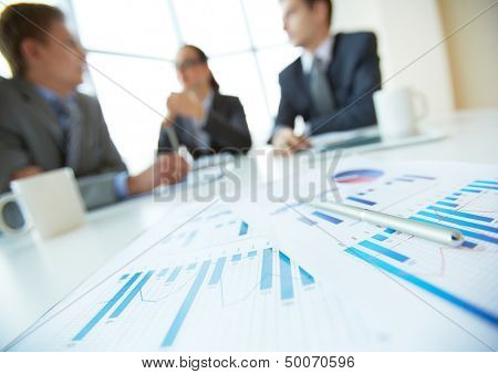 Close-up of business documents lying on the desk, office workers meeting in the background