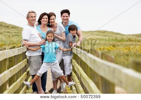 Multi Generation Family Walking Along Wooden Bridge