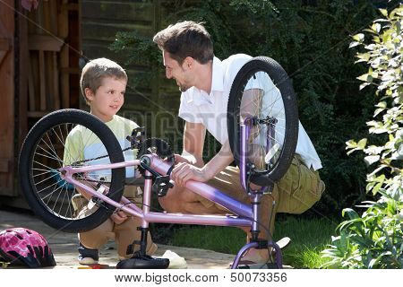 Father And Son Mending Bike Together