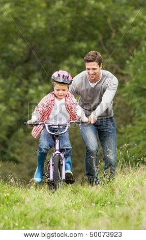 Father Teaching Son To Ride Bike In Countryside