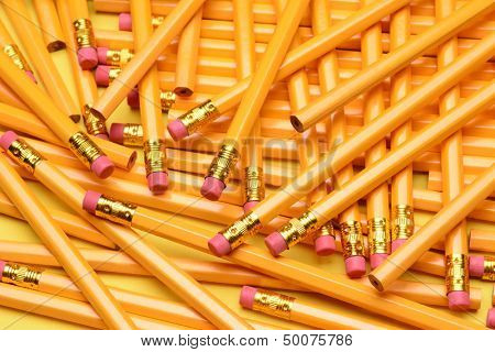 A random pile of pencils. Brand new pencils scattered on a yellow surface. Great for back to school projects.
