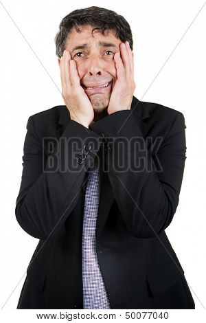 Griefstricken businessman holding his face in his hands as he cries to himself with a woebegone expression, isolated on white
