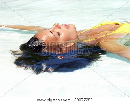 Young woman relaxed and floating on water.Taking sun.