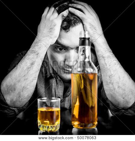 Monochromatic image of a drunk and melancholic hispanic  man with his hands on his head
