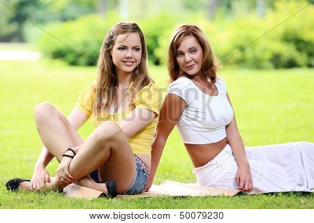 Two beautiful girls having fun on a picknick in a park