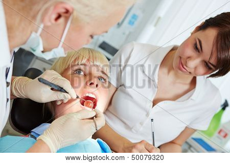 Dentist giving dental treatment with probe and mirror and dental assistant watching
