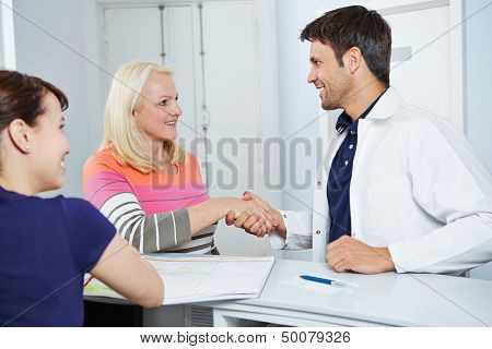 Smiling doctor giving senior female patient handshake to say goodbye