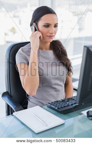 Serious gorgeous businesswoman on the phone in her office