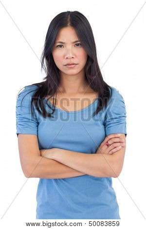 Annoyed asian woman with arms crossed on white background