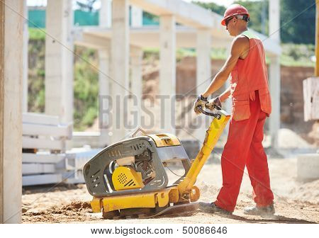 builder worker compacting soil with vibration plate compaction machine during pavement roadwork
