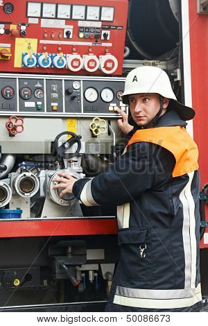Fireman in uniform operating fire engine or fire truck on duty during training