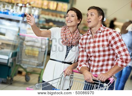 Family couple with trolley cart in meat grocery supermarket during weekly food shopping