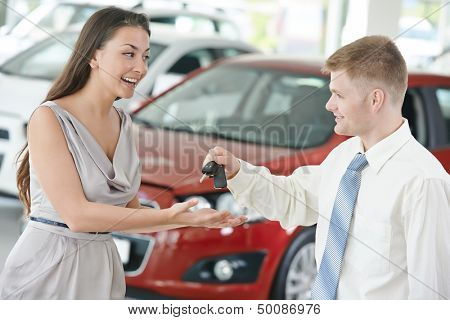 salesperson demonstrating new automobile car to young woman